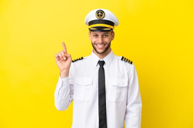 最高の兆候を示して指を持ち上げて黄色の背景に分離された飛行機の白人パイロット