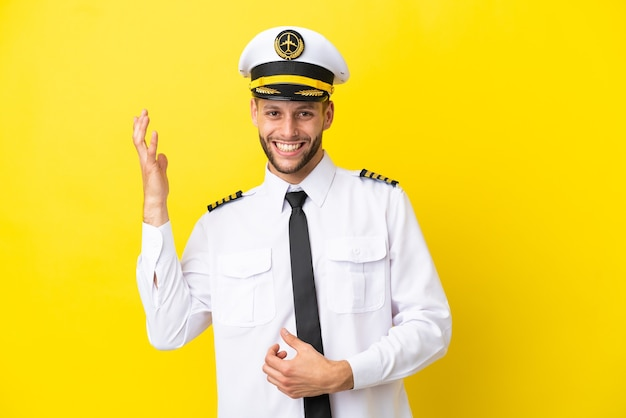 Airplane caucasian pilot isolated on yellow background making guitar gesture