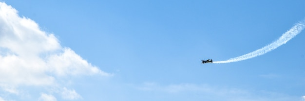 Airplane doing acrobatics in blue sky leaves a smoke