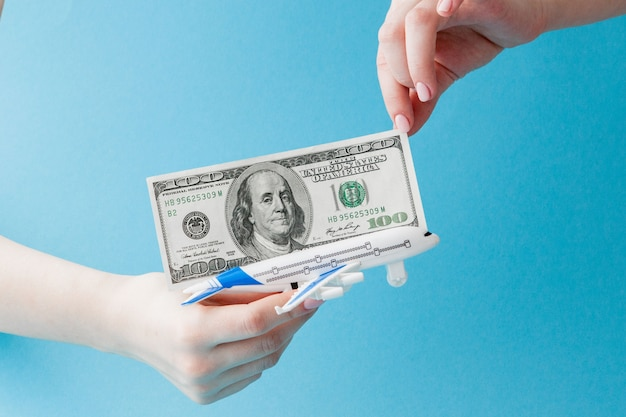 Airplane and dollars in woman hand on a blue background. travel concept, copy space