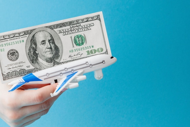 Airplane and dollars in woman hand on a blue