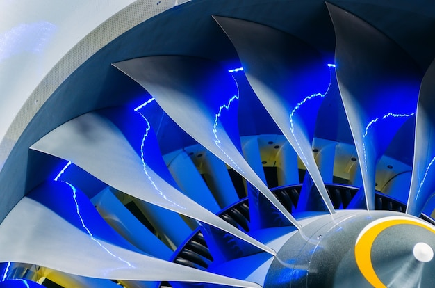 Airplane engine and blades with blue backlight close up.