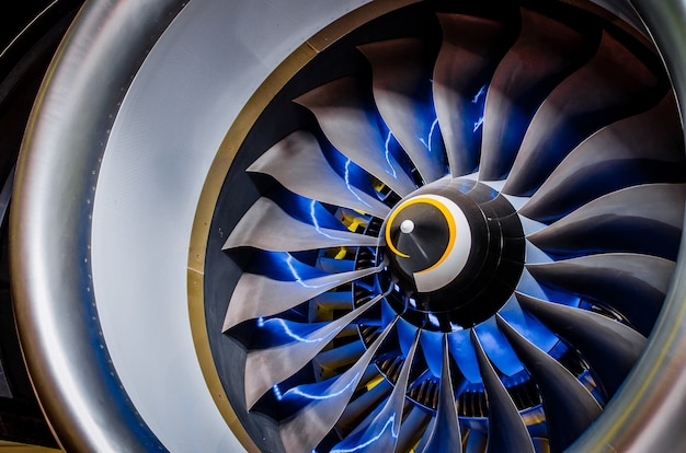 Airplane engine and blades with blue backlight illumination close up.