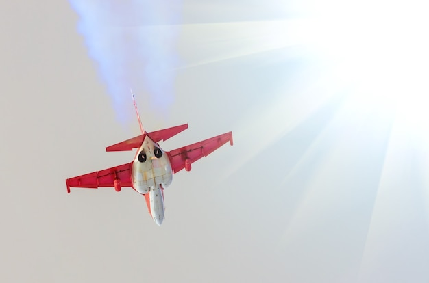 飛行機の戦闘機は、太陽のそばの空でジェット機と煙を出します。
