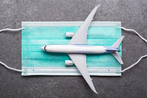 Полет на самолете с маской для профилактики корнонаавируса. взлет на борт нового нормального, безопасного для вашего здоровья. путешествие, туризм, защита путешественников от covid-19 с помощью масок.