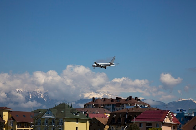 Airplane fly over buildings plane over the roofs of houses and mountains. mountain holidays