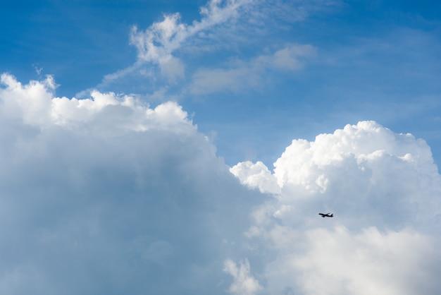 飛行機は大きな白い雲と日光と青い空を飛ぶ