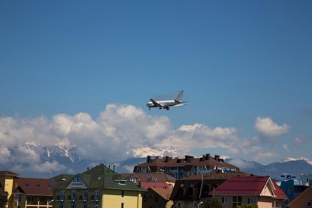 비행기는 건물 위로 날아 집과 산의 지붕 위에 비행기입니다. 산악 휴가