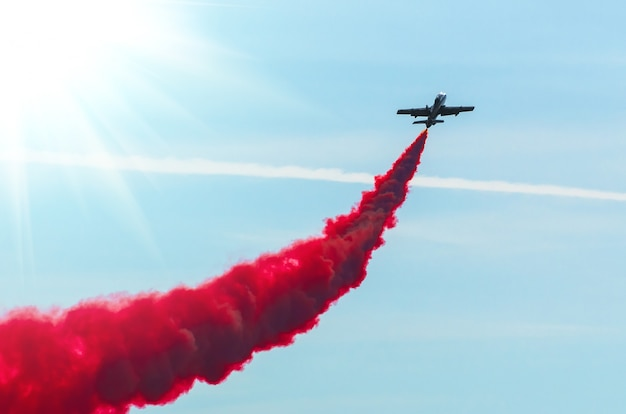 Airplane fly in zigzags with a red trail smoke in the sky.