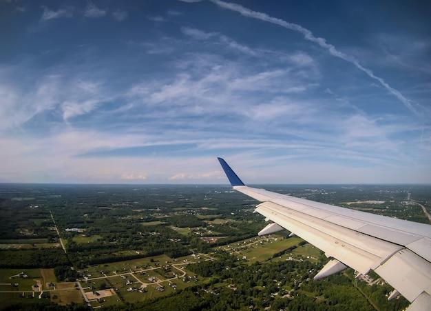 青い空に航空機の翼で雲の上を飛んでいる飛行機。
