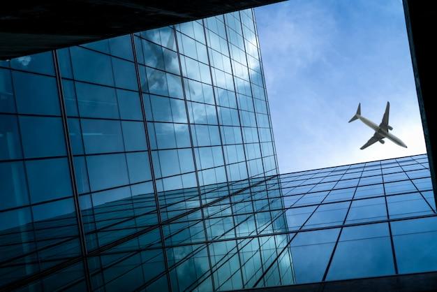 ガラス張りのモダンなオフィスビルの上を飛んでいる飛行機。未来的なガラスの建物の斜視図。ガラス張りのオフィスビルの外観。出張。会社の窓。