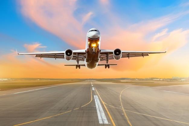 밝은 붉은 일몰 동안 저녁에 활주로에 도착하는 비행기가 활주로에 착륙합니다.