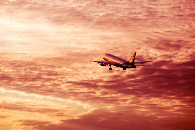 Airplane flying away in awesome cloudy sunset sky vacation concept