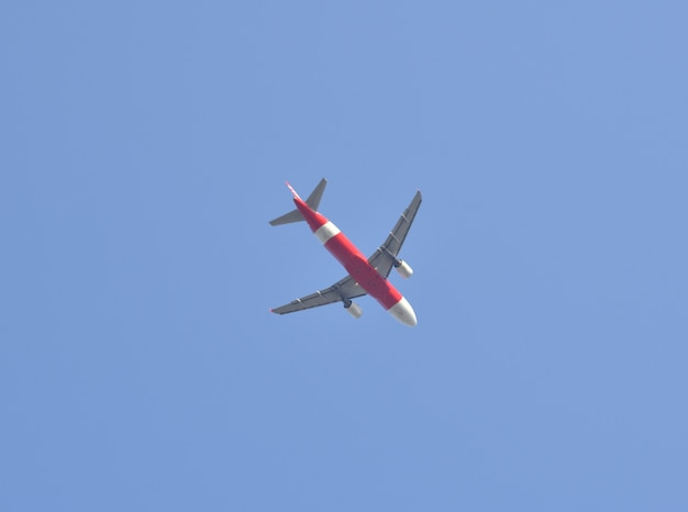 Airplane flying away to the blue sky