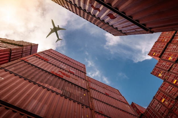 Airplane flying above container logistic.