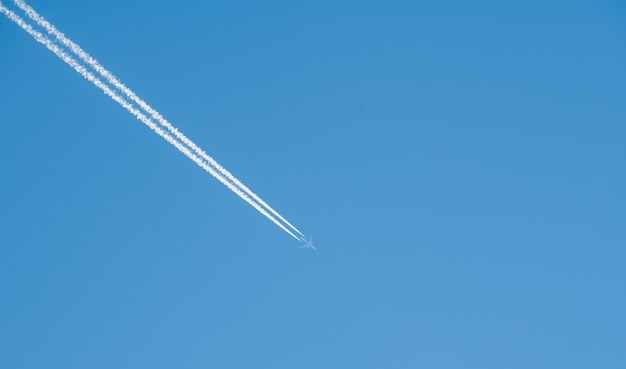 Airplane flying high in the blue sky
