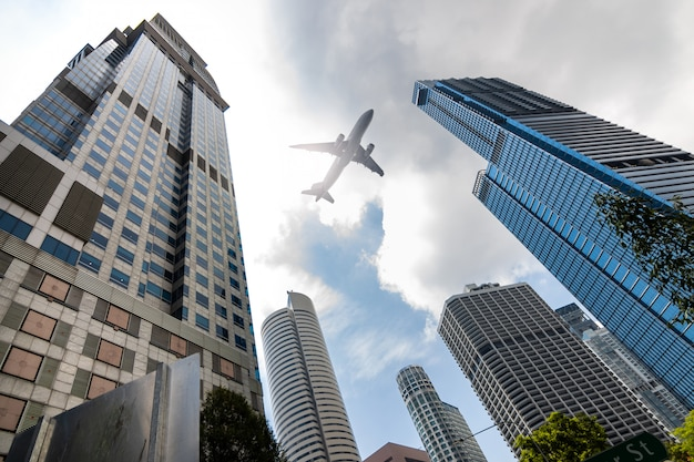 Airplane flying low over highrise office buildings