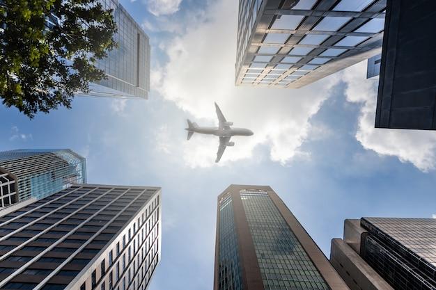 高層オフィスビルの上空を飛んでいる飛行機