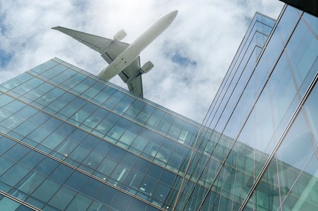 Airplane flying above modern office building. exterior facade of skyscraper building. business trip. reflection in transparent glass windows. aviation business after coronavirus vaccine injection.