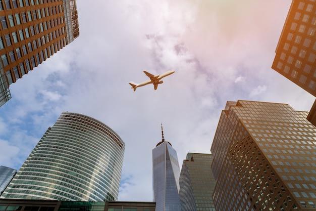 ダウンタウンの都市の建物の上を飛んで飛行機
