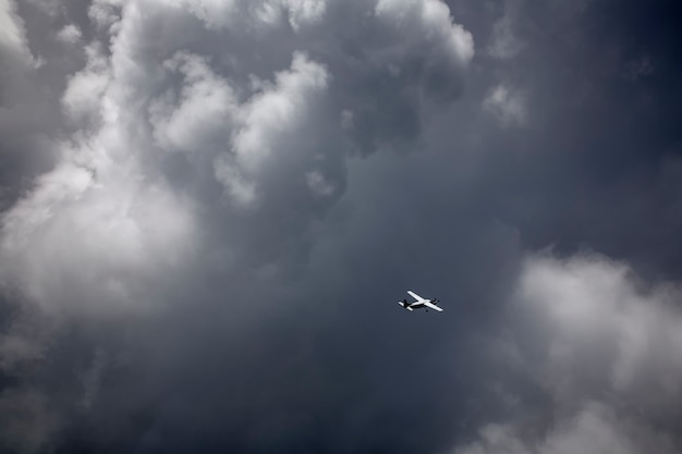 An airplane flying through the storm cloud in the sky.