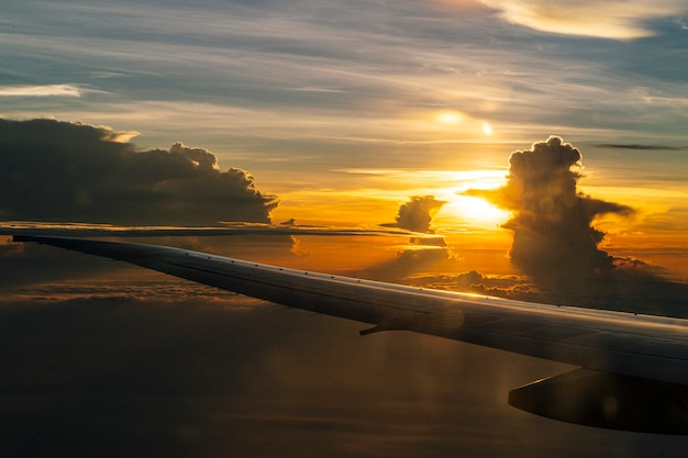 Airplane flying view from inside window on sunset time. beautiful horizon. traveling concept