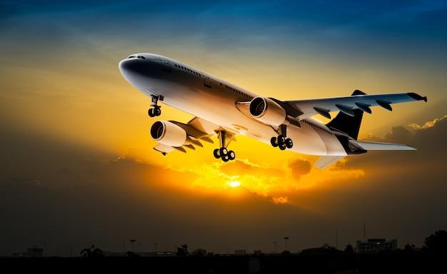 夕焼け空を飛ぶ輸送用飛行機
