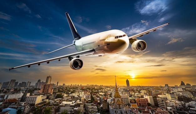 美しい夕日を背景に街の上空を飛ぶ輸送用飛行機