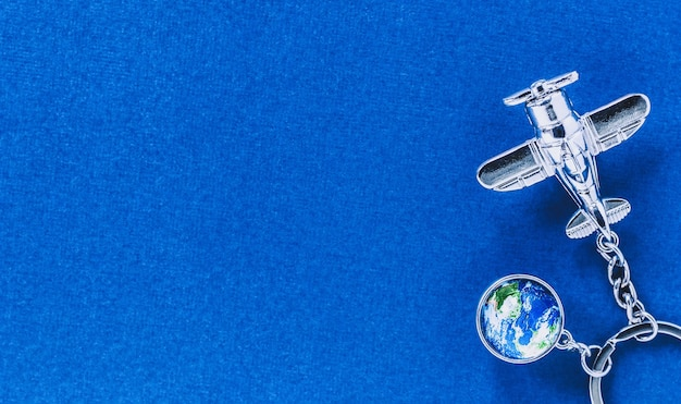 Airplane and globe models on blue with place for travel arrangement concepts