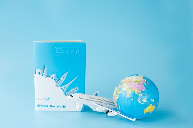 Airplane, globe and passport on blue surface
