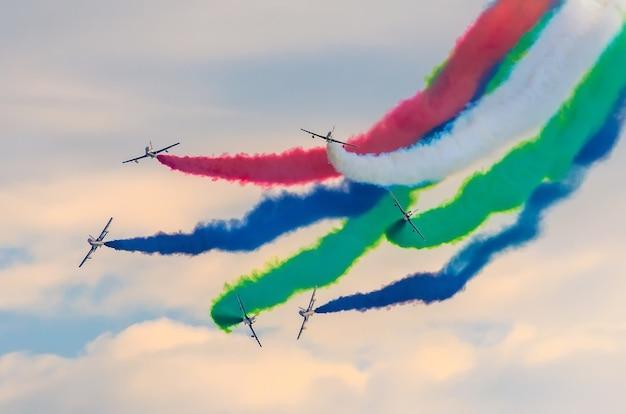 色の煙を背景にした飛行機のグループ戦闘機。