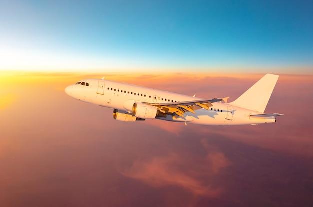 空高く飛ぶ飛行機は、夕方の光と日没の間に雲の上を飛ぶ。