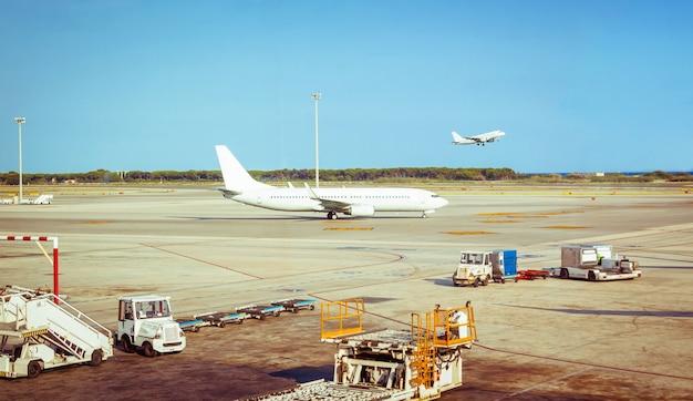 비행 준비가 된 활주로에 있는 비행기와 배경에서 이륙하는 다른 비행기