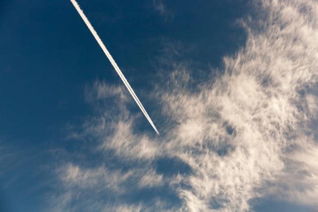 Самолет в небе сфотографирован самолет во время полета, в небе видны белые линии от двигателей расфокусированные