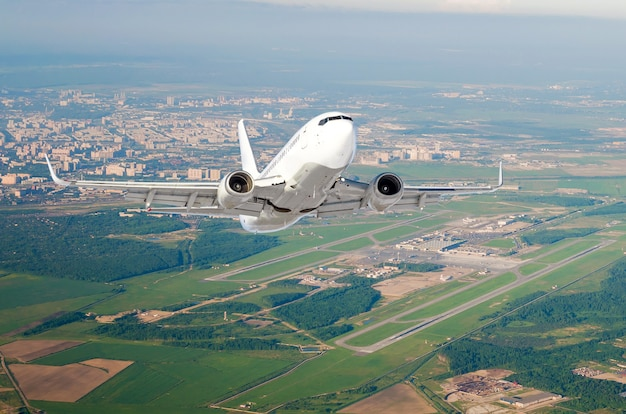 Airplane is climb flight level high view in the air, the airport of the runway, city, fields, forests and roads.