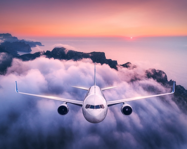 Airplane is flying over clouds at sunset in summer. landscape with passenger  airplane, low clouds, sea, purple sky at dusk