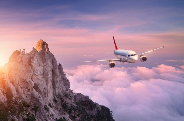 Самолет пролетает над облаками на закате. пейзаж с белым пассажирским самолетом, скалами, морем и фиолетовым небом с солнцем летом. приземляется пассажирский самолет. деловая поездка. коммерческий самолет