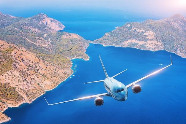 Самолет летит над островами и берегом моря на закате летом.