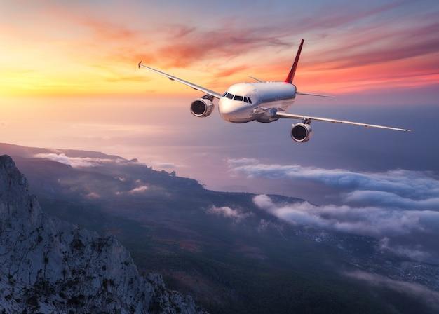 Самолет летит над низкими облаками на закате. пейзаж с пассажирским самолетом, горами, морем и оранжевым небом с красными облаками летом. пассажирский самолет. деловые поездки в европу. коммерческий самолет.