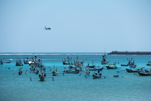 Airplane landing on airport and jukung fishing traditional boat in bali