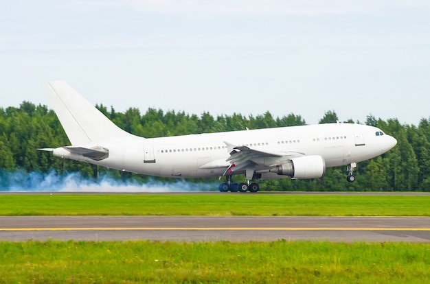 Airplane landing on the runway at the airport with smoke from the chassis