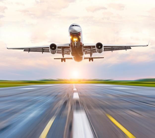 日没の夜明けの空港の滑走路への飛行機の着陸速度。