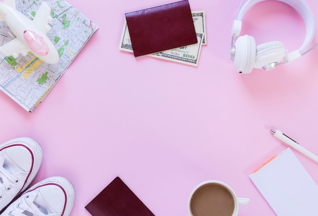 Airplane; map; passport; banknotes; footwear; earphone; tea; paper and pen on pink background