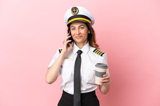 Женщина-пилот самолета средних лет изолирована на розовом фоне, держа кофе на вынос и мобильный