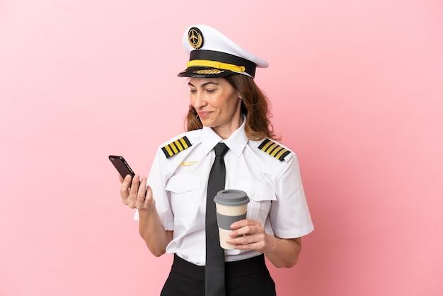 持ち帰り用のコーヒーと携帯電話を保持しているピンクの背景に分離された飛行機の中年パイロットの女性
