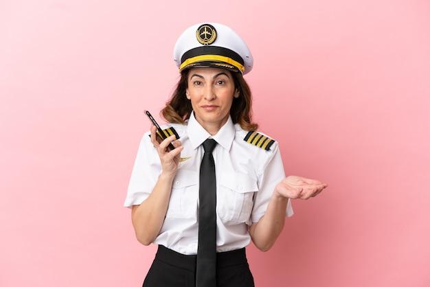 Женщина-пилот самолета средних лет изолирована на розовом фоне, разговаривает с кем-то по мобильному телефону