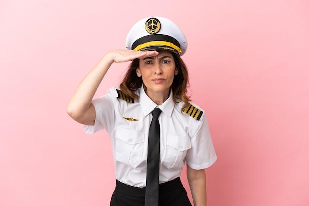 何かを見るために手で遠くを見てピンクの背景に分離された飛行機の中年パイロットの女性