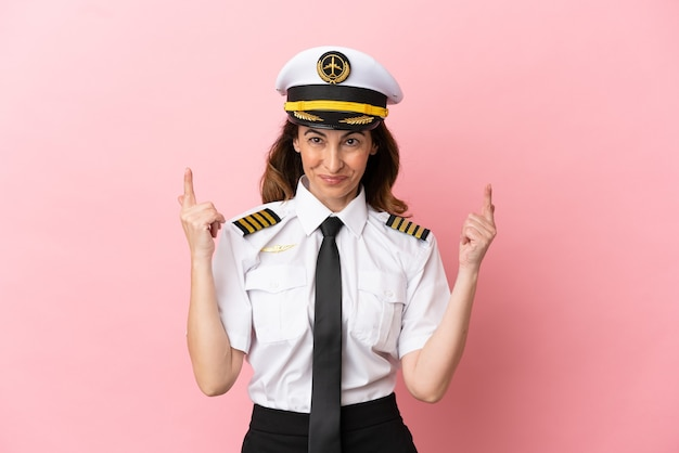 素晴らしいアイデアを指しているピンクの背景に分離された飛行機の中年パイロットの女性