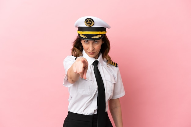 ピンクの背景に分離された飛行機の中年パイロットの女性は自信を持ってあなたに指を指しています