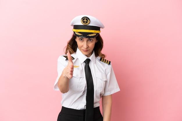 Женщина-пилот самолета средних лет изолирована на розовом фоне, пожимая руку для заключения хорошей сделки